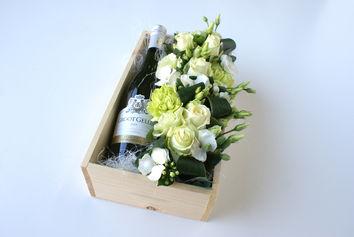 Bloemencreatie met fles witte wijn